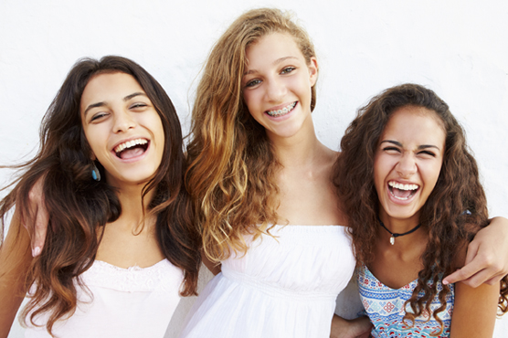 Portrait Of Three Teenage Girls Leaning Against Wall  Smiling To Camera